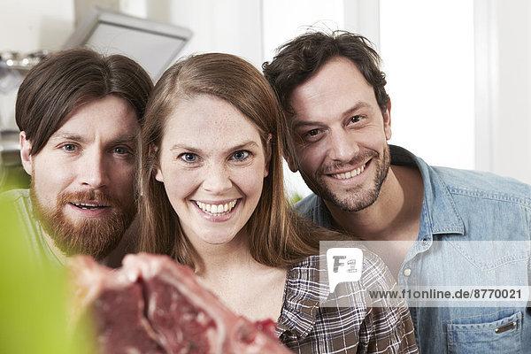 Porträt von drei Freunden in der Küche mit Steak