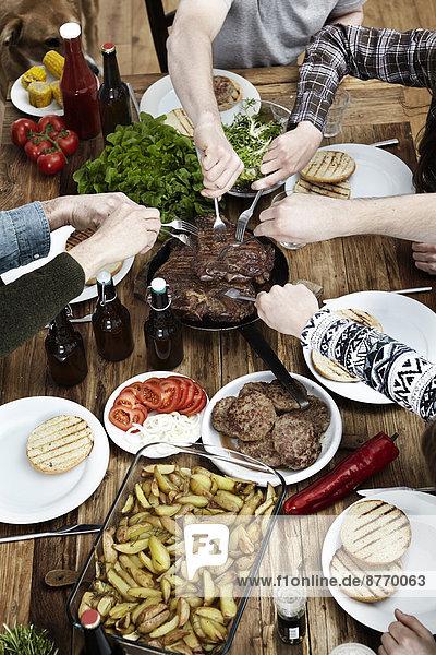 Freunde essen Kartoffeln  Steaks und Fleischbällchen an einem Holztisch.