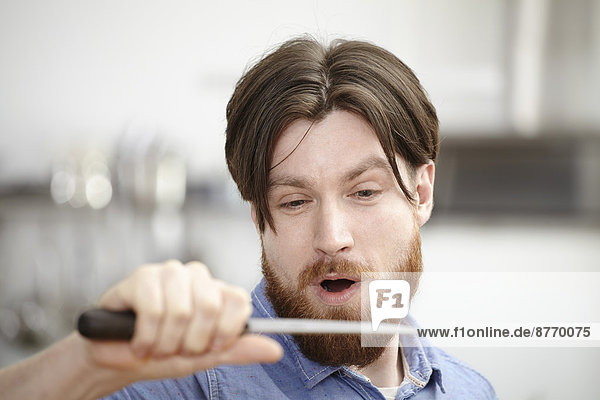 Man in kitchen holding knife