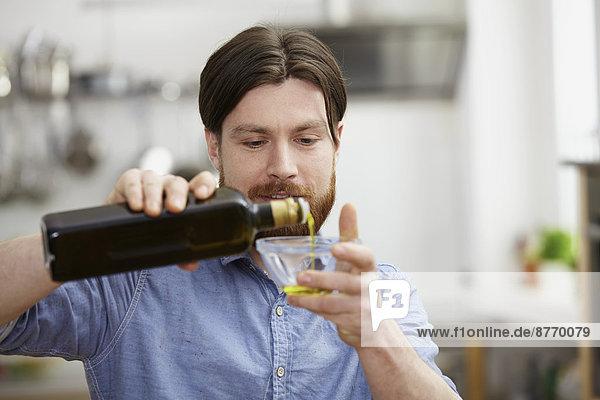Mann in der Küche gießt Olivenöl in die Schale