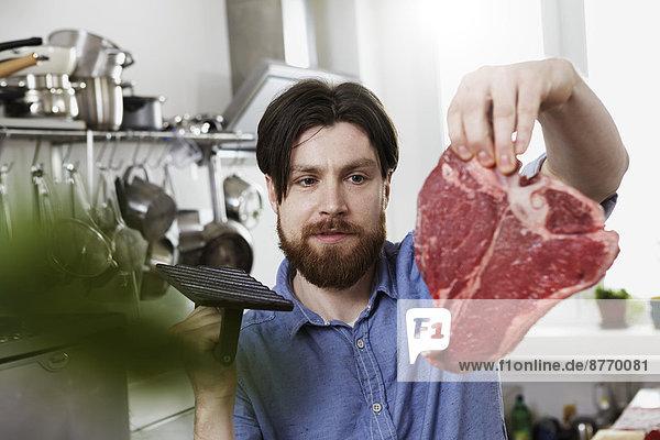 Mann in der Küche mit Steak