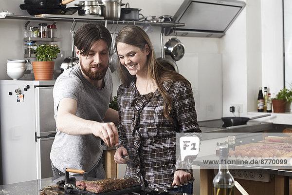 Paar Zubereitung von Steak in der Küche