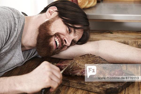 Glücklicher Mann  der auf dem Tisch liegt und ein großes Steak betrachtet.