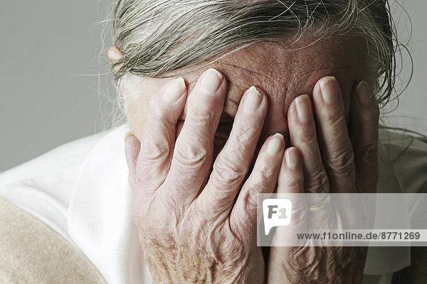 Seniorenfrau  die das Gesicht mit den Händen bedeckt.
