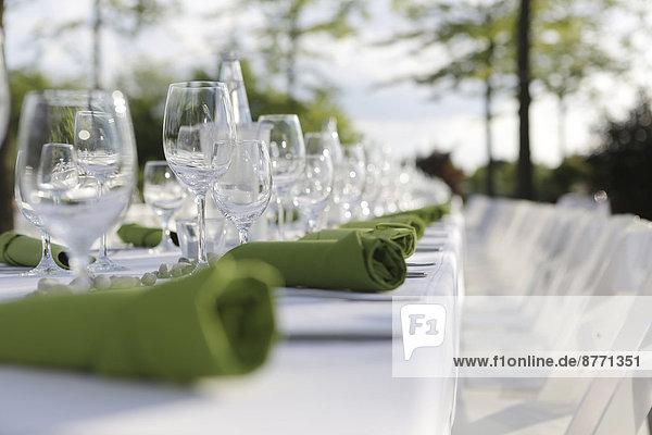 Festlich gedeckter Tisch mit grünen Servietten und Weingläsern  Teilansicht
