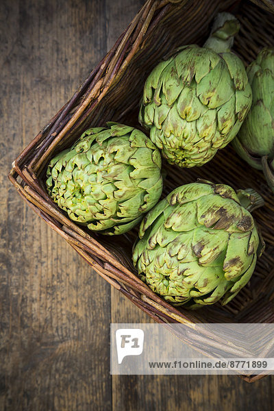 Basket of organic artichokes on wooden table  view from above
