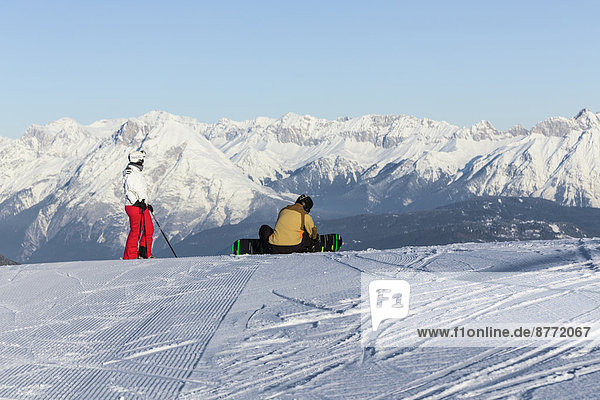 Austria  Tyrol  Innsbruck  Stubai Alps  view to Axamer Lizum with two skiers in front