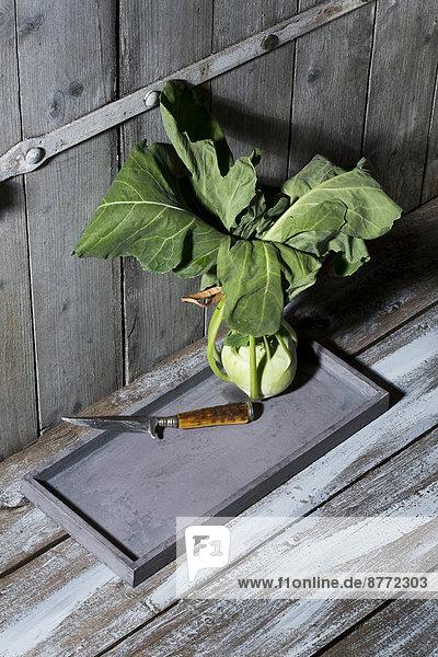 Kohlrabi (Brassica oleracea) und Messer auf Holzplatte