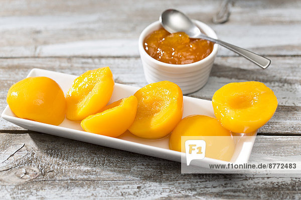 Bowl of peach jam and plate with halves of peaches on wooden table