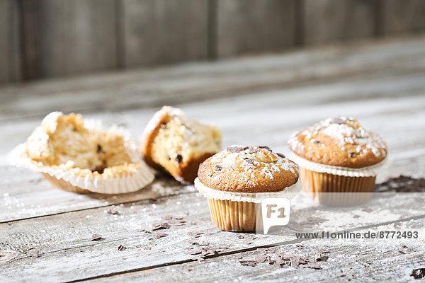 Zwei Muffins in Pappbechern und ein halber Biss im Hintergrund auf einem grauen Holztisch.