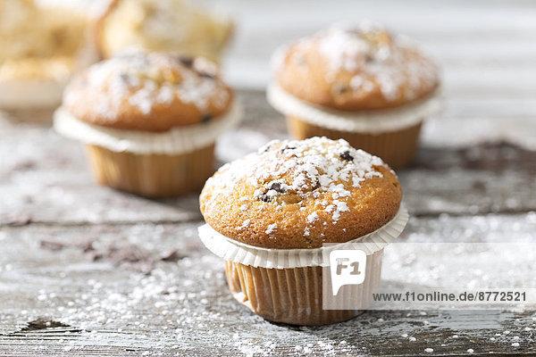Muffins in Pappbechern mit Puderzucker bestreut auf Holztisch