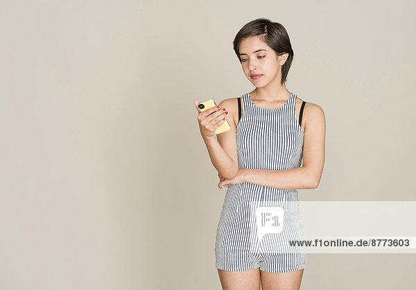 Nachdenkliche junge Frau liest eine SMS auf ihrem Handy