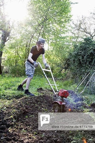 Mann  der im Bio-Garten arbeitet.
