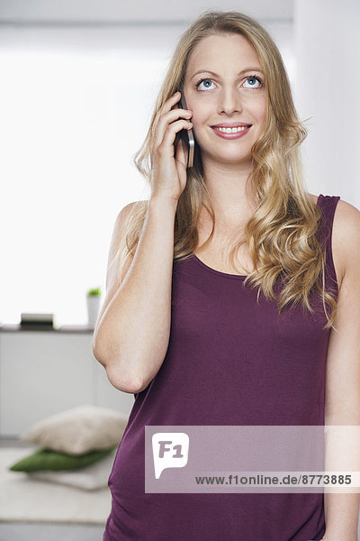 Portrait of young woman leaning against wall telephoning with smartphone
