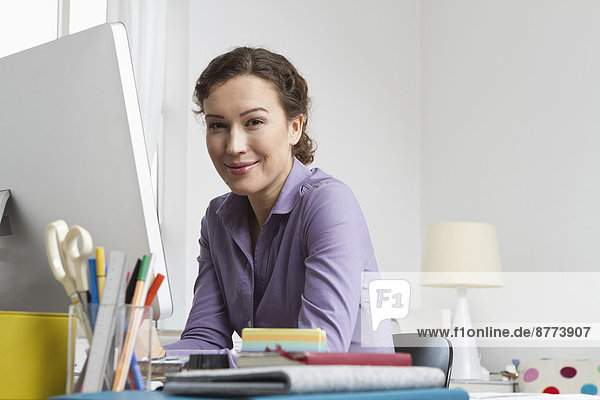 Woman at home sitting at desk with computer