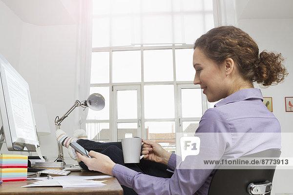 Frau am Schreibtisch bei einer Kaffeepause