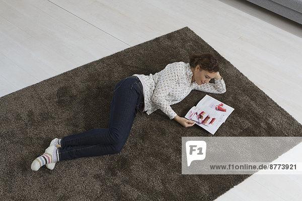 Woman lying on carpet reading magazine