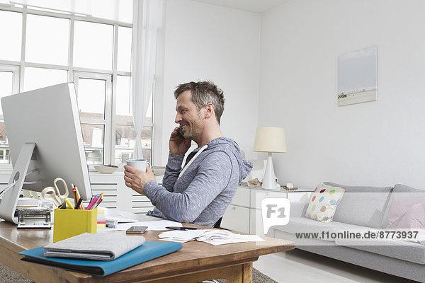 Mann am Schreibtisch am Telefon
