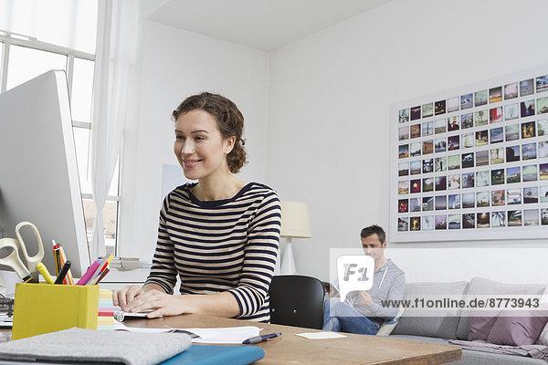 Frau zu Hause am Schreibtisch sitzend mit Computer und Mann im Hintergrund