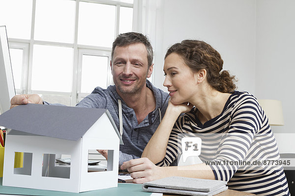 Couple at home with model house