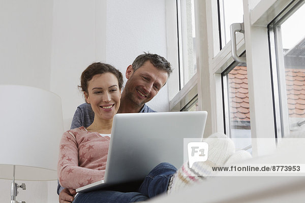 Couple sitting on windowsill using laptop