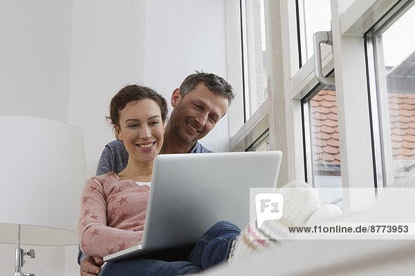 Couple sitting on windowsill using laptop