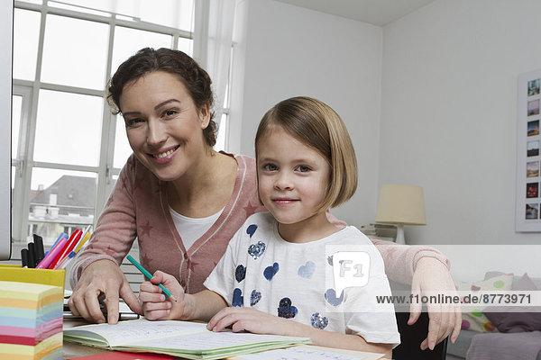 Porträt der Mutter mit Tochter am Schreibtisch
