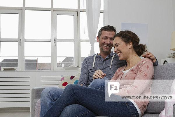Glückliches Paar auf der Couch sitzend