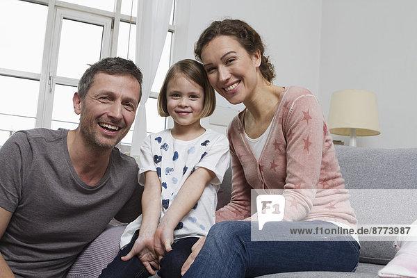 Mutter  Vater und Tochter zu Hause auf der Couch