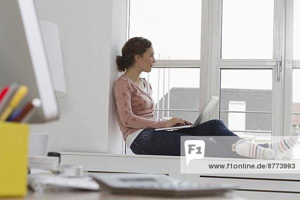 Frau sitzt auf der Fensterbank mit Laptop