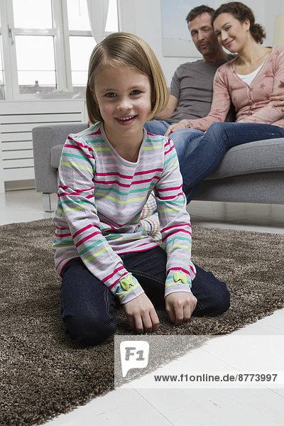 Blondes Mädchen im Wohnzimmer mit Eltern im Hintergrund