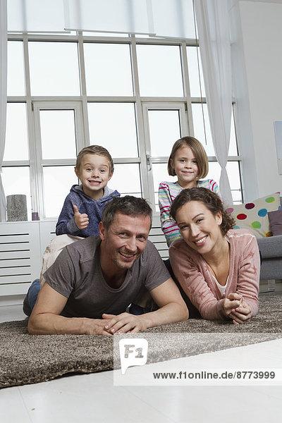 Glückliche vierköpfige Familie im Wohnzimmer