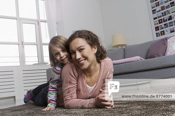 Glückliche Mutter und Tochter auf Teppich im Wohnzimmer liegend