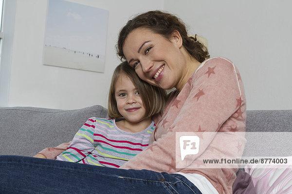 Glückliche Mutter und Tochter auf der Couch sitzend