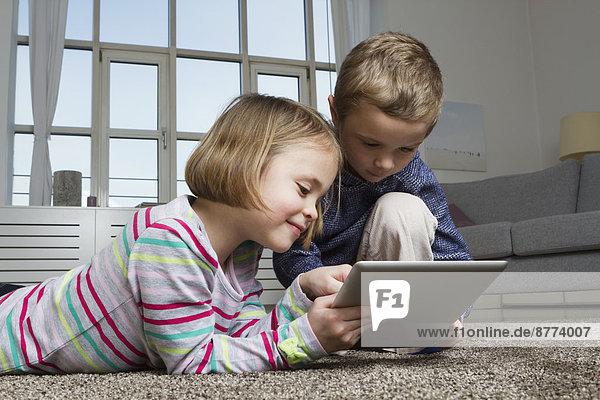 Geschwister mit Tablet-Computer auf Teppich im Wohnzimmer
