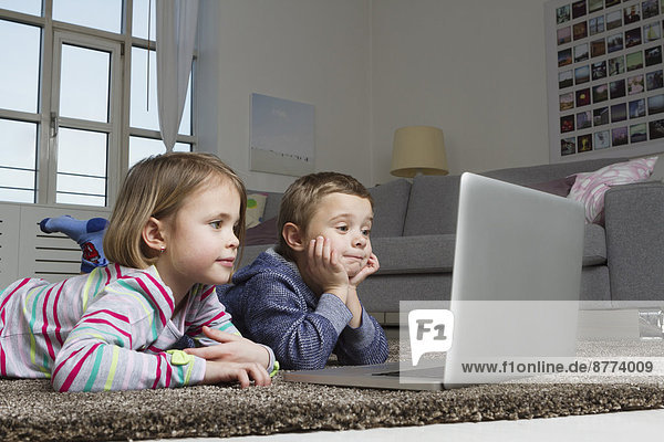 Brother and sister using laptop on carpet in living room