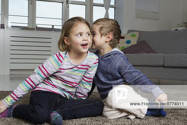 Geschwister flüstern auf Teppich im Wohnzimmer
