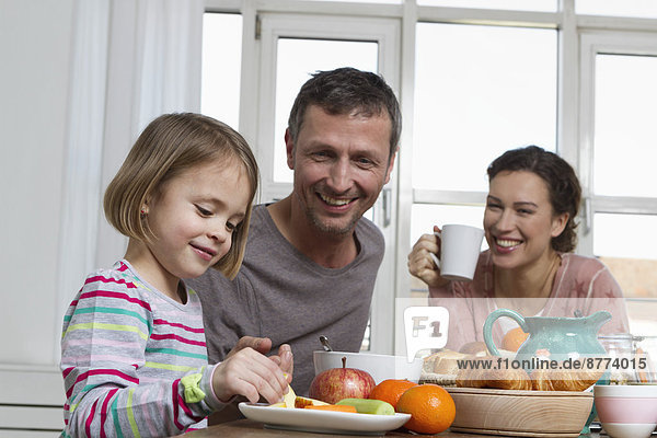 Father  mother and daughter having healthy breakfast