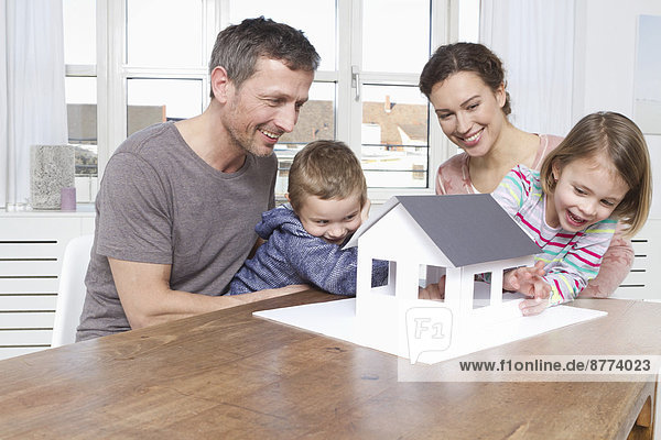 Family of four looking at house model