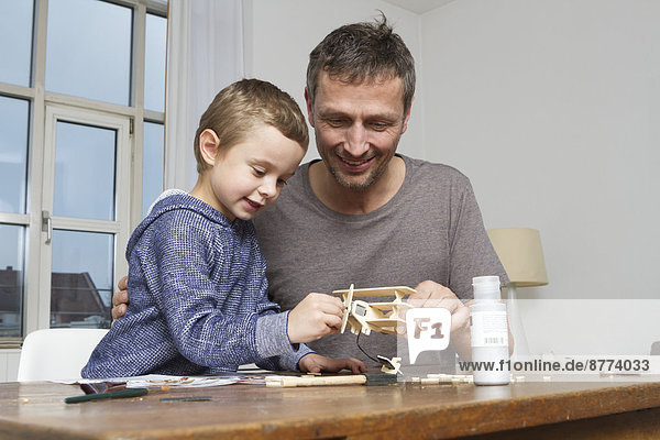 Father and son tinkering model airplane