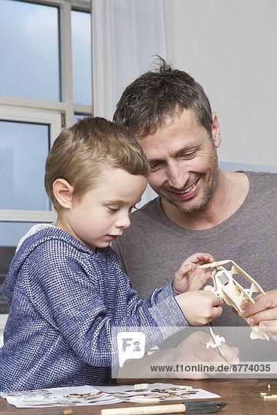 Vater und Sohn basteln Modellflugzeug