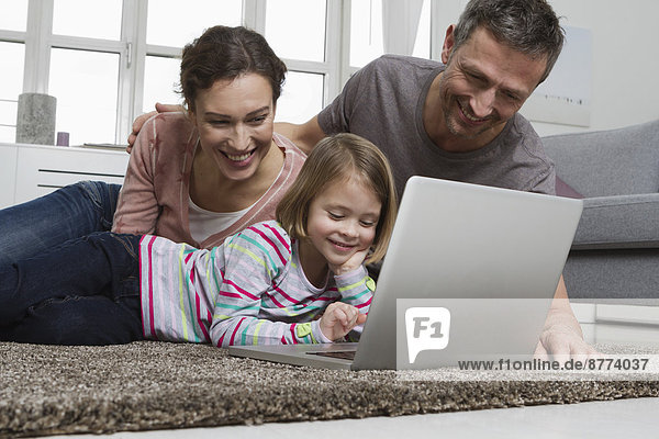 Father  mother and daughter using laptop on carpet in living room