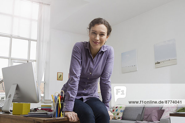 Woman at home sitting on desk with computer