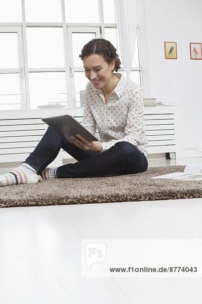 Frau zu Hause mit Tablet-Computer