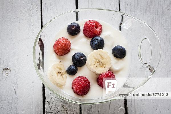 Glasschale aus Naturjoghurt mit Blaubeeren  Himbeeren und Bananenscheiben auf Holztisch