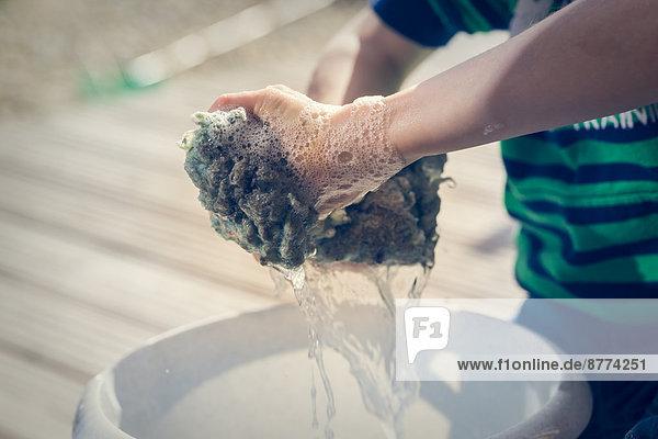 Hände des kleinen Jungen,  der das Reinigungstuch auswringt.