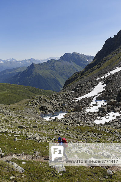 Austria  Vorarlberg  Woman hiking at Grafierjoch  Schmalzberg and Valiserapitze in background