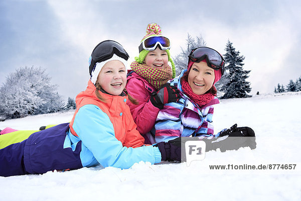 Germany  Masserberg  Mother and daughters lying in snow  smiling happily