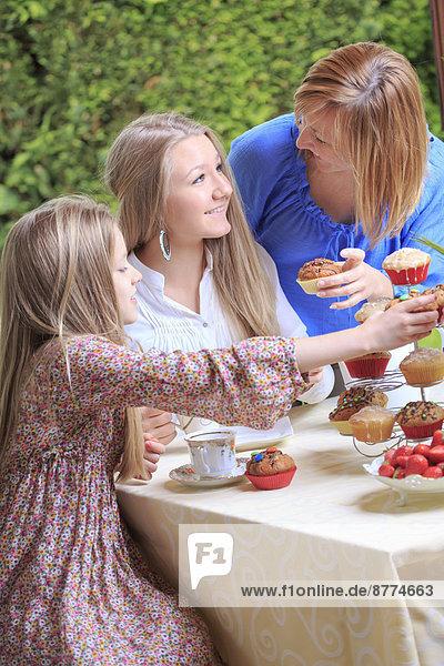 Mutter und ihre beiden Töchter essen Muffins.
