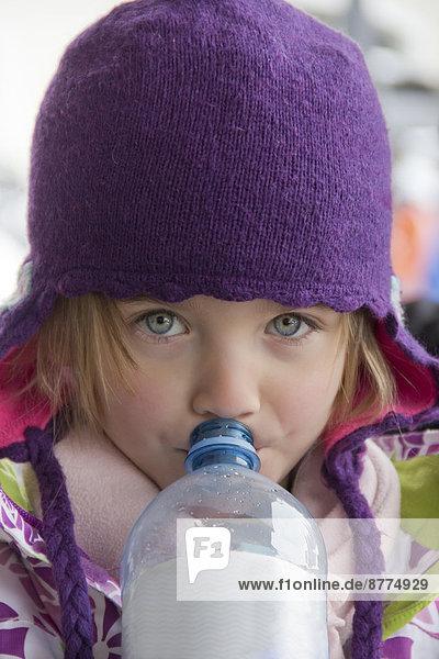 Porträt eines kleinen Mädchens  das aus einer Wasserflasche trinkt.
